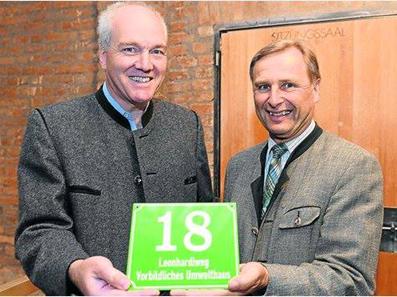Hans-Georg Hecker von der KlimaschutzOffensive Fischbachau übergibt die erste Grüne Hausnummer an den 1. Bürgermeister der Gemeinde, Josef Lechner.