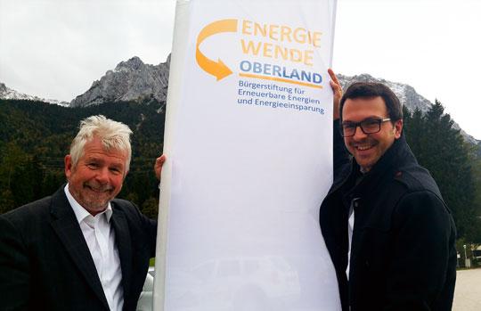 Josef Kellner (Vorsitzender des Vorstands; links im Bild) und Stefan Drexlmeier (Leiter der Geschäftsstelle; rechts im Bild) hissen die EWO-Fahne im Landkreis Garmisch-Partenkirchen