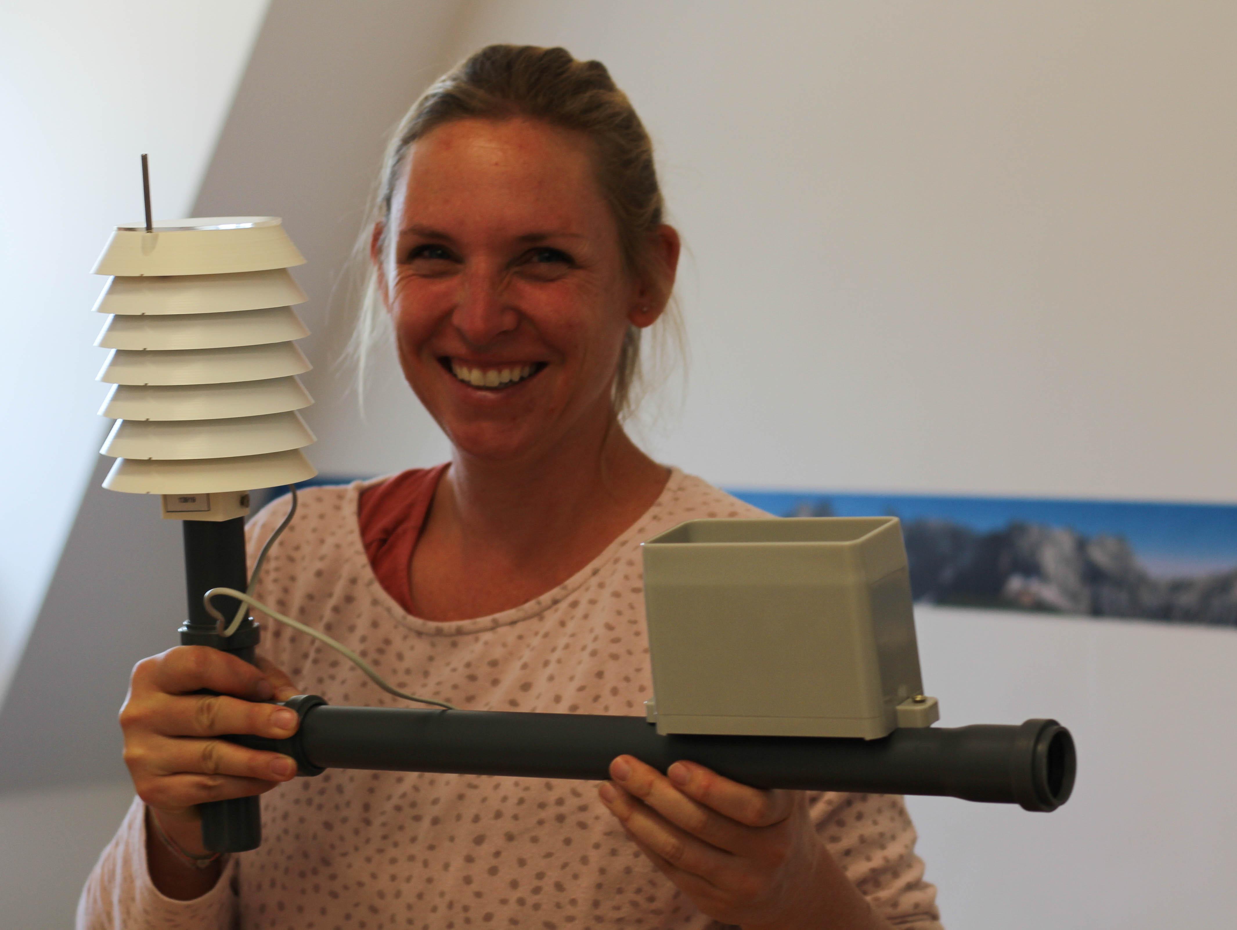 Dr. Cornelia Baumann von der Energiewende Oberland hält ein selbst zusammengebautes Wettermessgerät in den Händen. Das Gerät kann auf dem Balkon oder im Garten aufgestellt werden